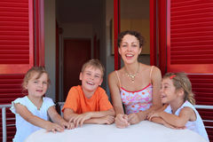 Woman with children sits in number on verandah. Woman with three children sits in number on verandah table with white table-cloth and laughs Royalty Free Stock Photo