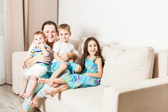 A woman with children are sitting on the couch. royalty free stock photo