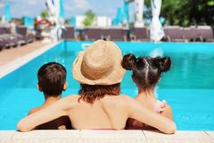 Woman with children in swimming pool. At resort royalty free stock photo