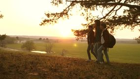Woman and children travel, walk in forest, admire the scenery at sunset. travelers mom and daughters travel with stock footage