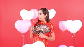 Woman in chinese dress with balloon. Isolated on red background stock footage