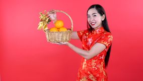 Woman in Qipao chinese dress. Woman with chinese dress oranges bag isolated on red background stock footage