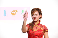 Woman in Chinese dress selects cosmetic on touch screen Royalty Free Stock Images
