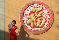 Woman in Chinese dress stand beside giant letter Stock Photos