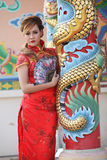 Woman in Chinese dress stand beside a pole Royalty Free Stock Photos