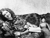 Woman in a Chinese print dress lying on the sofa with her dolls and a book Stock Images