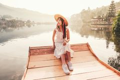 Woman with Chinese style boat in the lake with morning light and fog