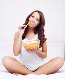 Woman with chips. Pretty woman eating potato chips in bed at home Royalty Free Stock Photo
