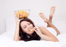 Woman with chips. Pretty woman eating potato chips in bed at home Stock Image