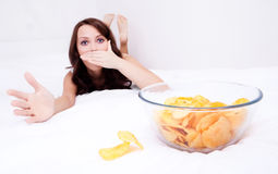 Woman with chips. Pretty woman willing to eat potato chips and scared of gaining weight,  in bed at home Stock Photos