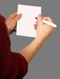 Woman with chit and pen. Detail of a woman holding paper chit and pen in grey back royalty free stock images