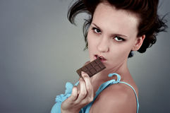 Woman and chocolate. Cheerful young woman eating chocolate Royalty Free Stock Photo