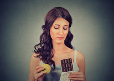 Woman with chocolate and apple trying to make a healthy choice control her body weight. Dieting concept royalty free stock photography