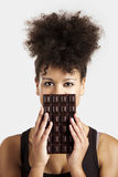 Woman with a chocolate bar Stock Image