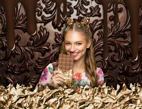 Woman with chocolate, brown sweet background. Young smiling woman in floral dress holds a bar of chocolate, vintage brown sweet background or texture with Stock Photo