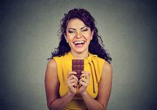 Woman with chocolate laughing. Isolated on gray background royalty free stock images