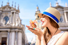 Woman with chocolate in Turin city. Young woman holding italian chocolate with bow on Turin city background. Turin in Piedmont region in Italy is famous of its royalty free stock image