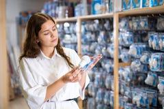 Woman choices energy saving lamp at hardware store