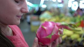 Woman choose one ripe dragon fruit and put it in shopping basket, Female customer at fruits on market, close up.  stock video