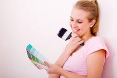 Woman choose paint color Stock Photos