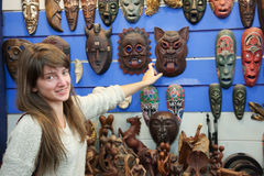 Woman chooses African mask Stock Photography