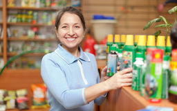 Woman chooses agricultural chemistry at  store Royalty Free Stock Photo