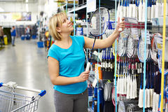 Woman chooses badminton racquet in shop Stock Image