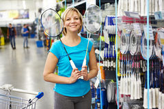 Woman chooses badminton racquet in shop Royalty Free Stock Image
