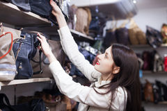 Woman chooses bag at shop Stock Photography