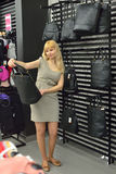 Woman chooses bag at the store. Blonde little wife at the store chooses handbag royalty free stock image