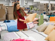 Woman chooses bed linen and bed in the supermarket mall. Customer woman chooses bed linen and bed in the supermarket mall store. She is taking pillow Stock Photos