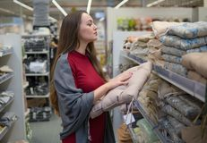 Woman chooses bed linen and bed in the supermarket mall. Customer woman chooses bed linen and bed in the supermarket mall store. She is examining sofa pillow Royalty Free Stock Photo