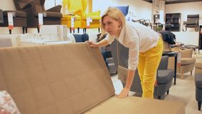 A woman chooses a bed in the store sofa stock video
