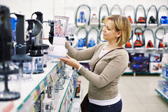 Woman chooses blender in store Royalty Free Stock Photo