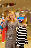 Woman chooses a blouse. The young beautiful woman in doubt - what blouse to buy Stock Photos