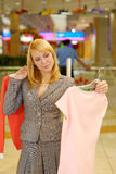 Woman chooses a blouse. The young beautiful woman in doubt - what blouse to buy Royalty Free Stock Image