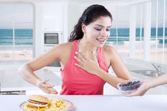 Woman chooses blueberry and refuse burger Stock Photography