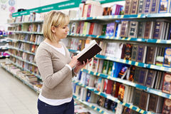 Woman chooses book in store Royalty Free Stock Image