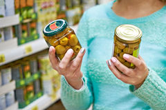 Woman chooses canned olives in grocery store Stock Photos
