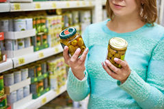 Woman chooses canned olives in grocery store Royalty Free Stock Photos