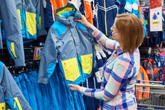 Woman chooses children winter jacket in sport shop. Woman chooses a children`s winter jacket in a sports shop stock images