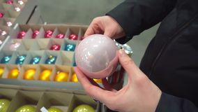 Woman chooses Christmas toys, holds in her hands rose ball.
