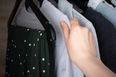 Woman chooses clothes for donate from wardrobe stock photos