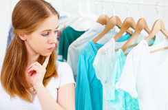 Woman chooses clothes in her wardrobe Stock Images