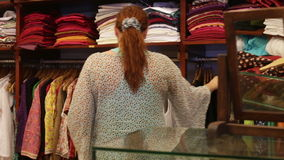 Woman chooses clothes in a shop stock footage