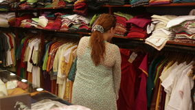 Woman chooses clothes in a shop stock video footage