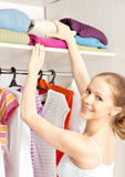 Woman chooses clothes in the wardrobe closet at home. Young woman chooses clothes in the wardrobe closet at home stock photography