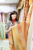 Woman  chooses draperies Stock Photos