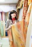 Woman  chooses draperies. At shop Stock Photos