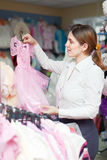 Woman  chooses  dress at children's clothes store Stock Image